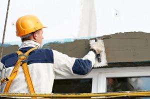 Tradesman at plastering a wall